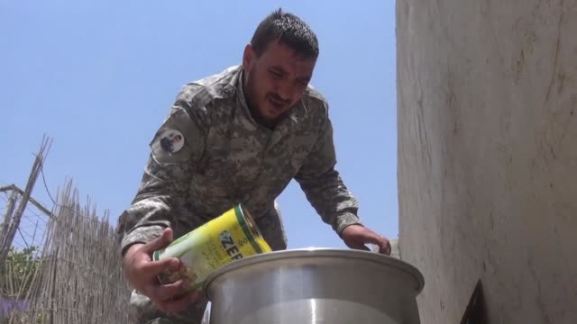on a day off from the raqa front line syrian fighter iskandar was busy chopping up chicken and garlic cloves for a steaming pot of homecooked... - syrian democratic forces stock videos & royalty-free footage