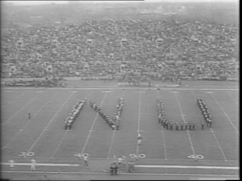 on a football field cheerleader form the letters 'nu' / cheerleaders perform a routine / during a play notre dame's elmer angsman runs the ball to... - nu stock videos and b-roll footage
