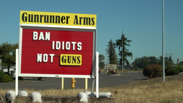 on a highway in oregon a gun shop displays a roadside sign in support of guns in the united states - gun shop点の映像素材/bロール