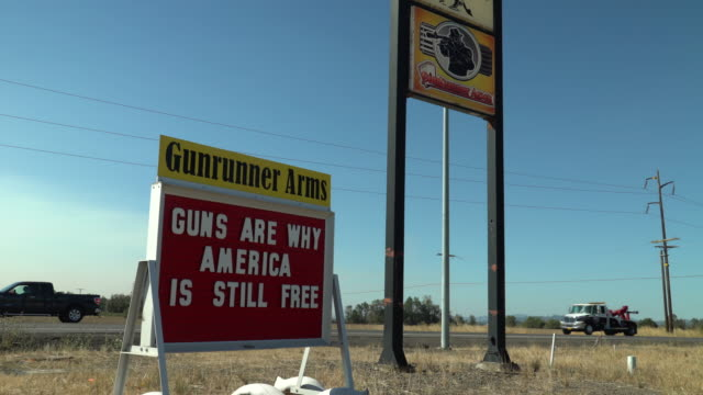 stockvideo's en b-roll-footage met on a highway in oregon a gun shop displays a roadside sign in support of guns in the united states - vuurwapenwinkel