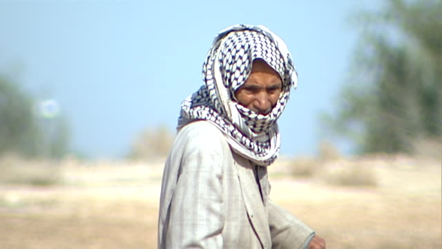 on a man wearing a checkered keffiyeh and sweeping the ground with a palm frond. since the 2003 gulf war occupying forces have caused irreparable... - frond stock videos & royalty-free footage