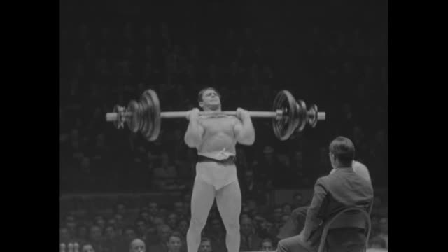 stockvideo's en b-roll-footage met on a stage at madison square garden, a weightlifter hoists large barbell with strenuous effort, is unable to hold it; he drops the barbell and falls... - zwaar