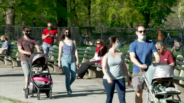 on a sunny day many people visited manhattan's central park amid the outbreak of the coronavirus disease some wore facial masks and practiced social... - two parents stock videos & royalty-free footage