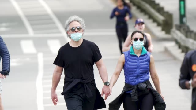 on a sunny day people exercising in manhattan's central park amid the outbreak of the coronavirus disease . some wore a protective face mask and... - sunny video stock e b–roll