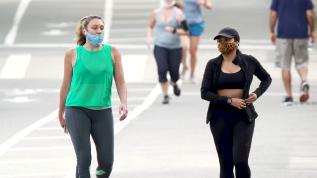 on a sunny day people exercising in manhattan's central park amid the outbreak of the coronavirus disease . some wore a protective face mask and... - パワーウォーキング点の映像素材/bロール
