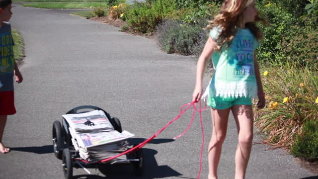 vídeos de stock e filmes b-roll de on a sunny spring day, frontal shot of young boy and girl delivering papers on a wagon, when dog runs out with leash on and boy grabs leash to control dog - kelly mason videos