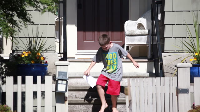 vídeos y material grabado en eventos de stock de on a sunny spring day, frontal shot of young boy delivering newspaper to a front door, then runs downs the stairs closing the gate behind him and proceeds to walk down the sidewalk. - kelly mason videos