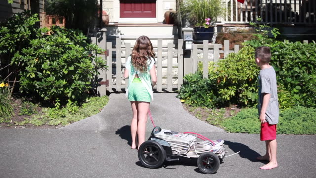 vidéos et rushes de on a sunny spring day, wide shot of girl and boy enter shot pulling cart with newspapers and they stop, read list on paper together, and move on to next house in white picket fence house neighbourhood - kelly mason videos