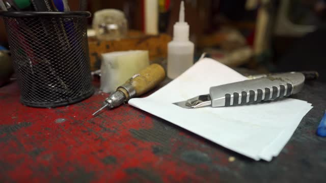 on a table in a cobbler workshop there are bottle og glue, scalpel and awl - scalpel stock videos & royalty-free footage