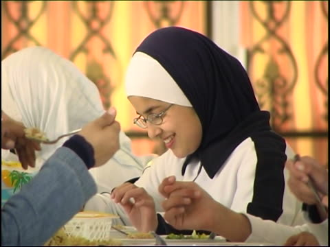 on a young shia orphan having her lunch with other girls all wearing the blue and white uniform of the imam sadr foundation. - tradition stock videos & royalty-free footage