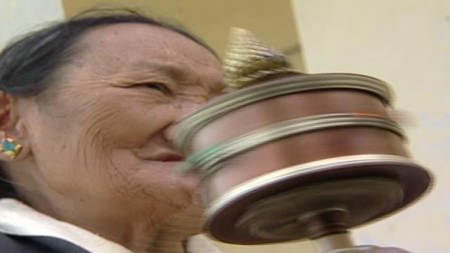 on an elderly tibetan woman chanting prayers and turning a prayer wheel. thousands of tibetan exiles live in dharamsala. - traditionally tibetan stock videos & royalty-free footage