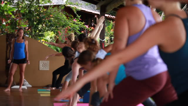 on an outdoor yoga deck surrounded by lush vegetation, a woman, teaching a yoga class to a line up of women on colourful yoga mats move from warrior pose to standing up. - kelly mason videos stock videos & royalty-free footage