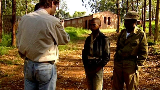 mark austin returns to rwanda 20yrs after reporting on the genocide itn lib austin chatting to people in the street austin talking to two boys arched... - face down stock videos & royalty-free footage