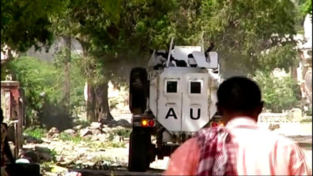 money transfer services to be cut; t22021205 / tx 22.2.2012 location unknown: white armoured vehicle as weapons fired from side burning remains of... - somalia stock videos & royalty-free footage