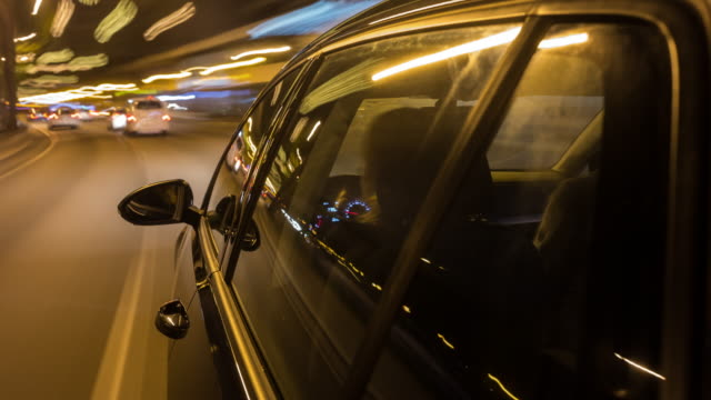 on board a driving german black car long exposure time lapse shot while night, camera looking in driving direction, windows with reflections in foreground, the background is motion blurred, female  driver partly seen but not recognisable through windows - wing mirror stock videos and b-roll footage