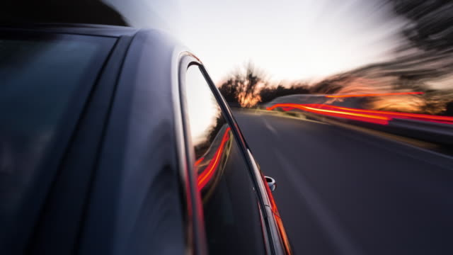 vídeos y material grabado en eventos de stock de on board a driving german black car time lapse shot while sunset, camera looking against the driving direction, windows with reflections in foreground, the background is motion blurred - retrovisor exterior