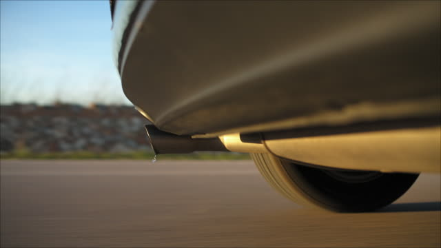 on board a driving german car video shot while sunset, camera mounted low under the rear bumper with the exhaust pipe and the left rear wheel tire prominent in frame, the background is motion blurred - fossil fuel stock videos & royalty-free footage