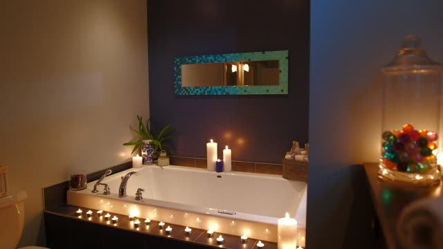 dolly in on candlelit bath - bagno caldo video stock e b–roll