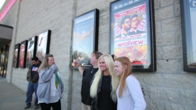 """on christmas day movie goers pose with poster outside jasper 8 theatres for """"the interview"""" which sony originally pulled after north korea allegedly... - christmas poster stock videos & royalty-free footage"""