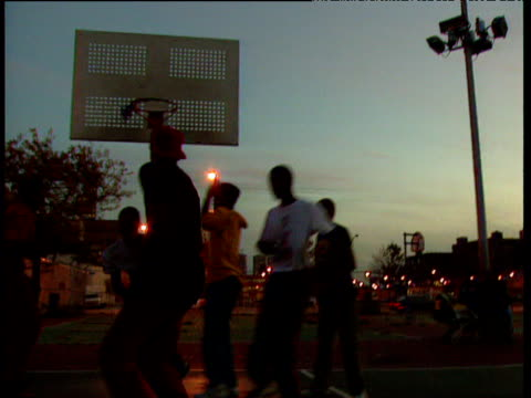on court with teenagers playing basketball silhouetted by dusky light chicago - 1987 stock-videos und b-roll-filmmaterial