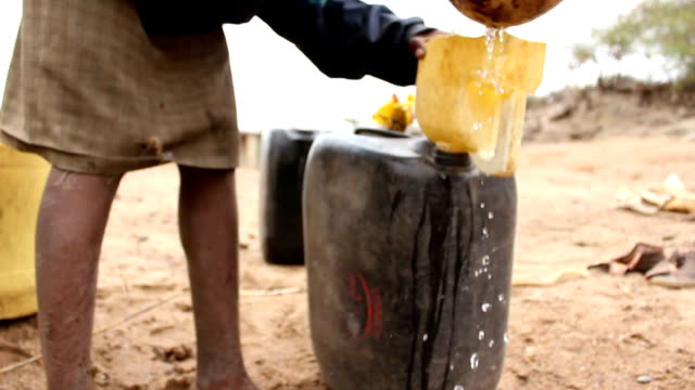 on dry river bank to fill up gallon boy getting water from a small well on august 02 2011 in road from garisa to dadaab kenya - アフリカの角点の映像素材/bロール