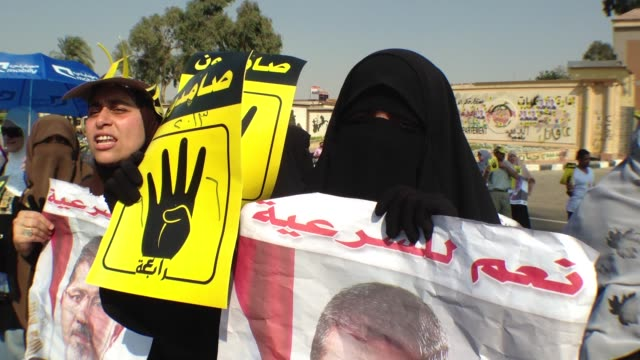 vídeos de stock, filmes e b-roll de ts on female supporters pan to crowd autos drive by drivers express support with four finger salute posters of morsi in cairo egypt - véu