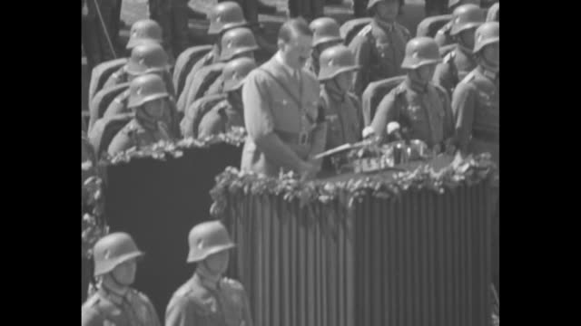 on grounds of tannenberg memorial , german chancellor adolf hitler holds papers in hand as he walks past german president paul von hindenburg's... - german military stock videos & royalty-free footage