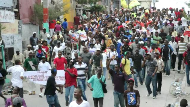 on haitian independence day protesters march through the streets of port au prince calling for the resignation of the president michel martelly - hispaniola stock videos & royalty-free footage