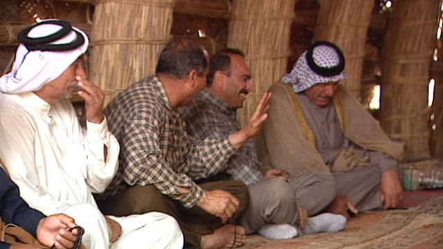 on marsh arab men chatting and laughing in a traditional village mudhif . mudhif architecture dates back to sumerian times. - bricco per il caffè video stock e b–roll