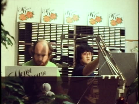 vidéos et rushes de p on phonograph record player/ ms american dj ron jacobs in the kkua radio station studio booth/ ms zo from volume unit meter and sound control panel... - platine de disque vinyle