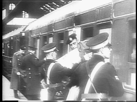 on rail station platform soldiers on stretchers are given cigarettes / soldiers are given newspapers food and drinks by red cross workers through... - marine stock-videos und b-roll-filmmaterial