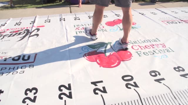 vidéos et rushes de ts on ruler used to measure how far cherry pits are spit in the cherry pit spitting contest includes audience - traverse city