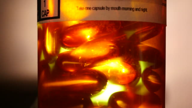 on rx label and capsules of hydroxychloroquinne glow and pulse inside a prescription bottle with donald trump's name on the label. this is a... - rx stock videos & royalty-free footage