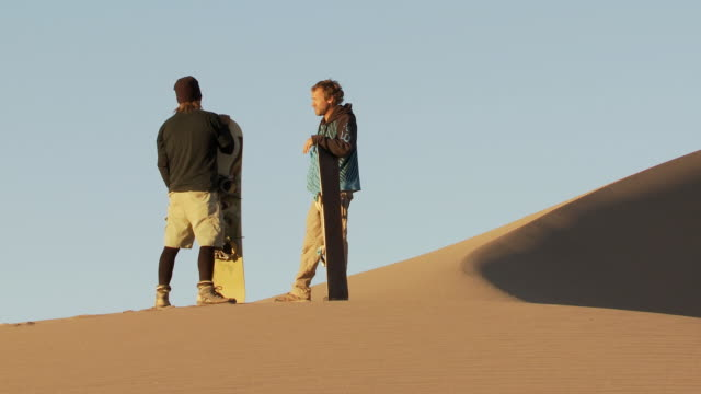 ms on sand dune two people standing with sandboarders looking around and talking / san pedro de atacama, norte grande, chile  - newoutdoors stock videos & royalty-free footage