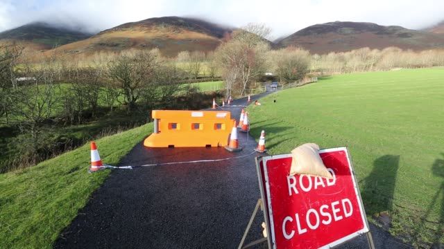 on saturday 5th december 2015, storm desmond crashed into the uk, producing the uk's highest ever 24 hour rainfall total at 341.4mm. it flooded many... - road closed englisches verkehrsschild stock-videos und b-roll-filmmaterial