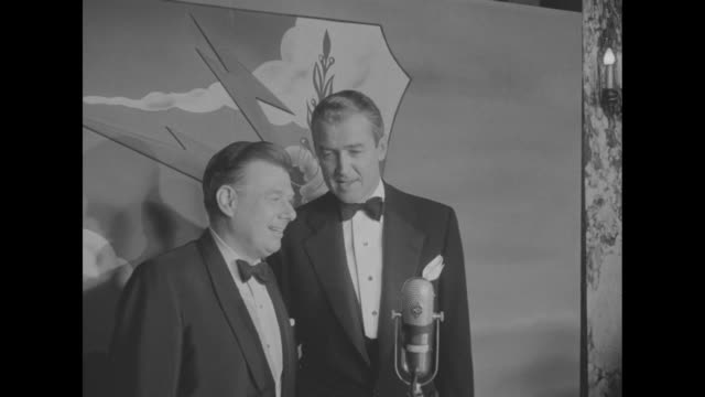 on stage inside theatre jimmy stewart and arthur godfrey at microphone in front of strategic air command logo / actress grace kelly joins them /... - grace kelly actress stock videos and b-roll footage