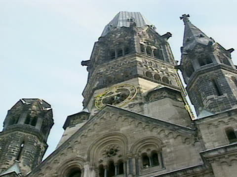 on steeples of kaiser wilhelm memorial church unidentifiable children lined up at base near arches. school field trip. - カイザー・ヴィルヘルム記念教会点の映像素材/bロール