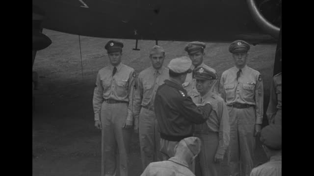 on tarmac of airfield next to plane gen douglas macarthur supreme commander of southwest pacific area pins distinguished service medal on general... - allied forces stock videos and b-roll footage