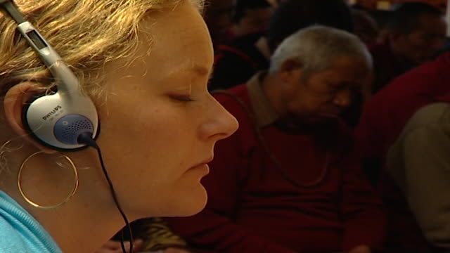 on the face of a causasian woman at tsuglagkhang temple listening to hh dalai lama giving a sermon on headphones. the 14th dalai lama lives in exile... - traditionally tibetan stock videos & royalty-free footage