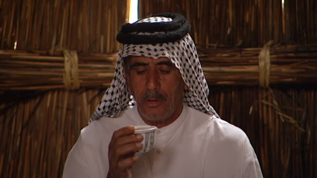 vídeos de stock, filmes e b-roll de on the face of a marsh arab man drinking coffee sitting on a carpeted floor under arches made of reed bundles in a traditional mudhif in southern... - oriente médio etnia