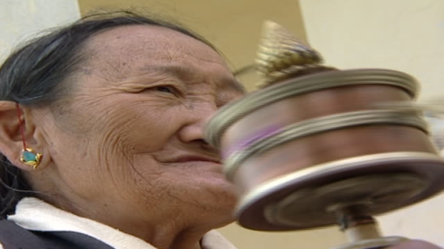 on the face of a wizened elderly tibetan woman turning a prayer wheel and chanting prayers. thousands of tibetan exiles live in dharamsala. - traditionally tibetan stock videos & royalty-free footage