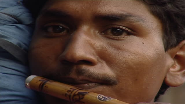 on the face of an indian street hawker playing a bansuri. this musical instrument is a side blown flute, made from bamboo found in many parts of... - rhythm stock videos & royalty-free footage