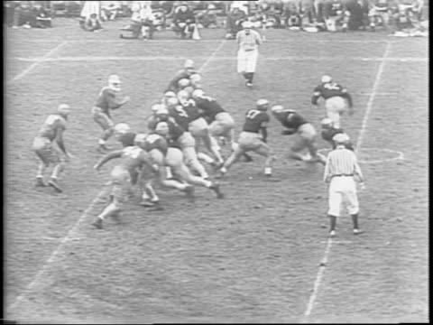 on the football field, army's arnold tucker passes to glenn davis who runs to the 45 yard line before being tackled / tucker passes to davis again,... - ウェストポイント点の映像素材/bロール
