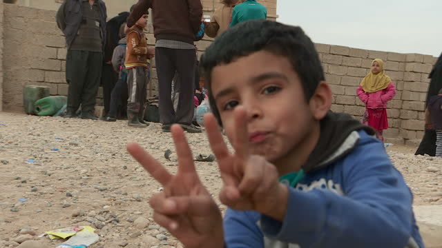 On The Front Line Of The Battle To Retake Mosul Showing Exterior shots civilians evacuating eastern parts of Mosul children showing peace sign and...