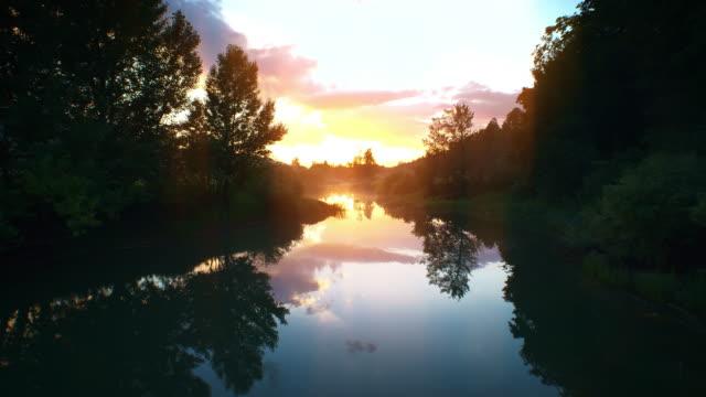ANTENNE sur la rivière vers le soleil levant d'or