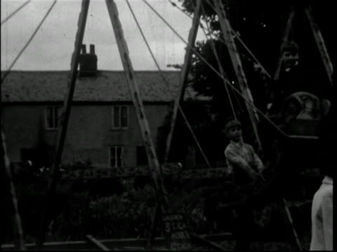 on the swings at shepperton fair, england, 1950s - surrey england stock videos & royalty-free footage
