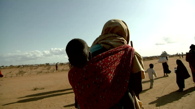 on their back upon arrival to refugee camp site Refugee women carrying children on July 30 2011 in Dadaab Kenya