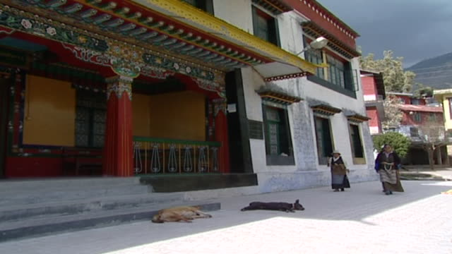 on tibetans circumambulating the library of tibetan works; two of them carry prayer beads and one carries a prayer wheel. the library holds over... - traditionally tibetan stock videos & royalty-free footage