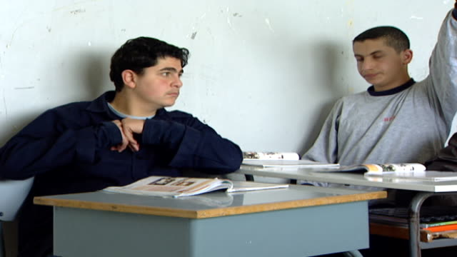 on two students at their desks with open textbooks in a classroom at irfan, a druze religious school with five branches in lebanon that operate as... - シャイフ点の映像素材/bロール