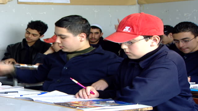 vidéos et rushes de on two students raising their hands, one of them wearing a red ball cap, in a classroom at irfan, a druze religious school with five branches in... - casquette de baseball
